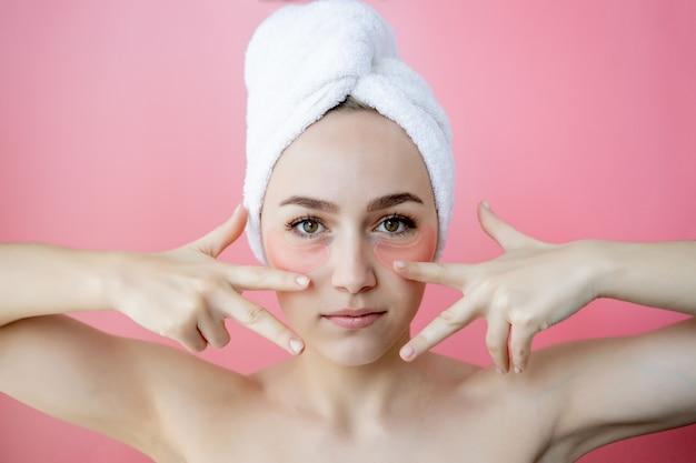 Studio shot van tevreden blanke sproeten vrouw, gekleed in witte handdoek op het hoofd, met collageen patches onder de ogen, naakt tegen roze achtergrond staan. huidverzorging, cosmetisch product concept