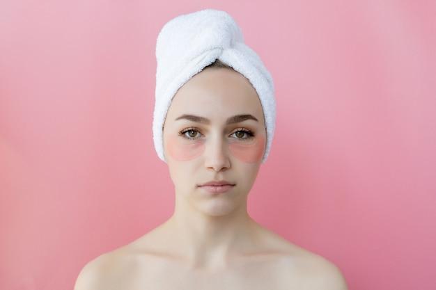 Studio shot van tevreden blanke sproeterig vrouw, gekleed in witte handdoek op het hoofd, met collageen patches onder de ogen, permanent naakt tegen roze achtergrond, cosmetisch product concept