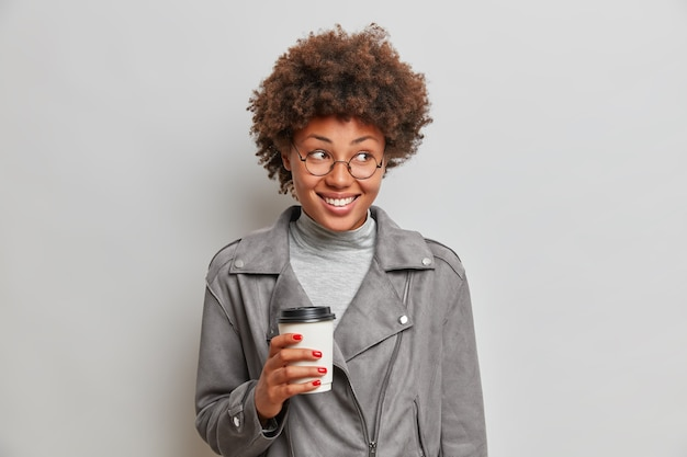 Studio shot van tevreden glimlachende afro-amerikaanse vrouw houdt papieren kopje koffie