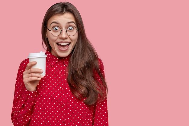 Studio shot van tevreden jonge vrouw lacht positief, drinkt afhaalkoffie, heeft pauze na lezingen