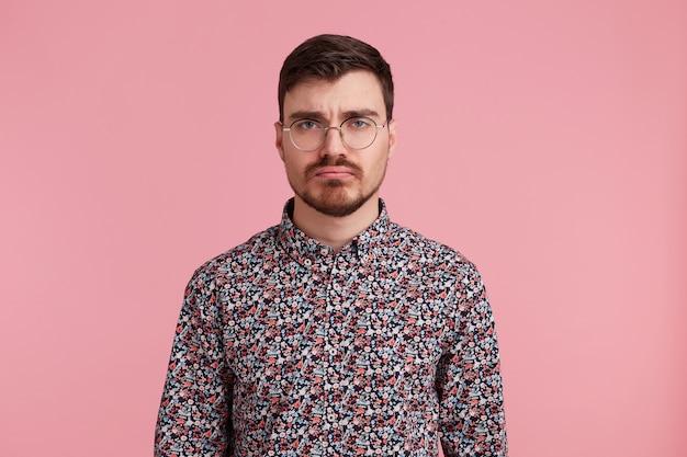 Studio shot van trieste jonge bebaarde man in glazen, gekleed in een kleurrijk shirt, geïsoleerd op roze achtergrond. mensen en emoties concept.