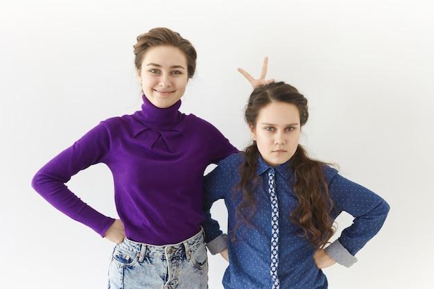 Studio shot van twee brunette zusters poseren tegen witte muur achtergrond: bejaarde meisje glimlachend breed gebaar maken