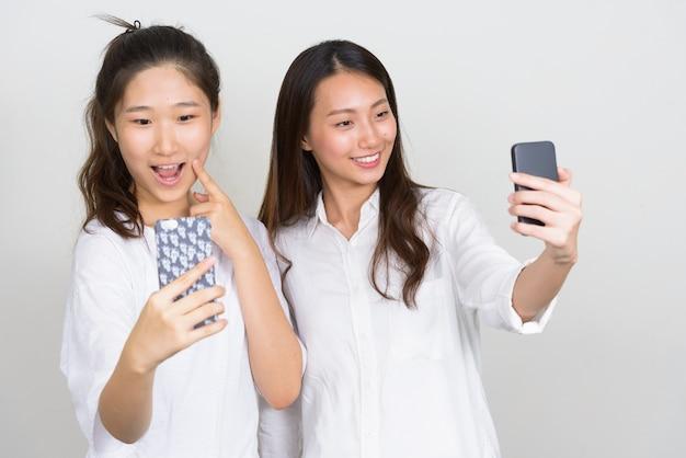 Studio shot van twee jonge mooie koreaanse vrouwen als vrienden samen tegen een witte achtergrond