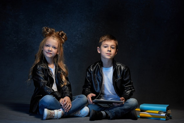 Studio shot van twee kinderen met tablet zittend op de vloer