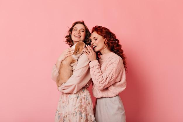 Studio shot van twee vrienden met hond. krullende meisjes spelen met puppy op roze achtergrond.
