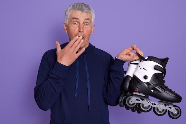 Studio shot van verbaasd witharige senior man met rolschaatsen in handen