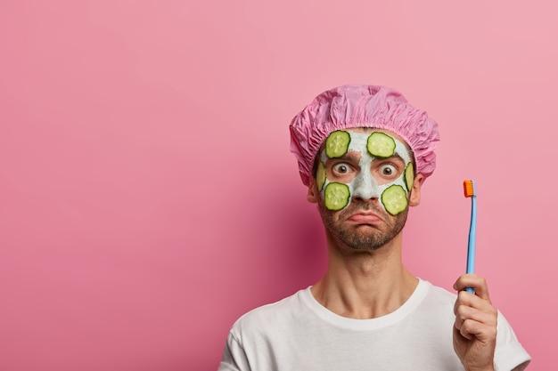Studio shot van verbaasde ongeschoren man geldt komkommers op gezicht, heeft een verjongingsbehandeling, poetst tanden, gekleed in vrijetijdskleding