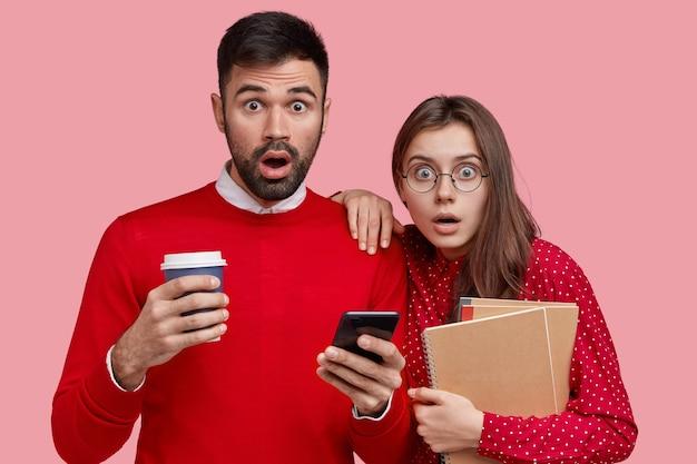Studio shot van verrast emotionele klasgenoten dragen rode kleding, staren naar de camera, houden mobiele telefoon vast, drinken afhaalkoffie, hebben pauze na het seminar