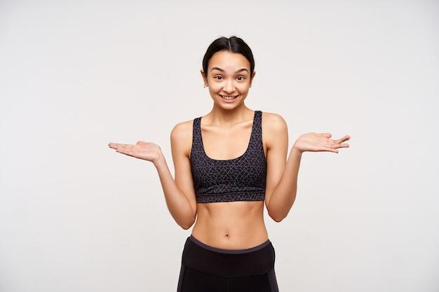 Studio shot van verwarde jonge donkerharige slanke vrouw glimlachend vrolijk terwijl schouderophalend met opgeheven handpalmen, staande over witte muur in sportieve kleding