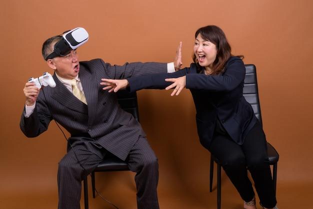 Studio shot van volwassen japanse zakenman en volwassen japanse zakenvrouw samen tegen bruine achtergrond