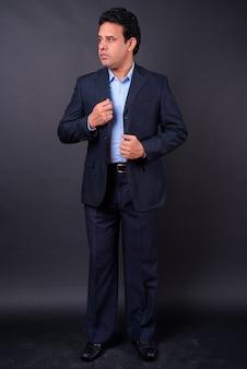 Studio shot van volwassen knappe indiase zakenman in pak tegen zwarte achtergrond