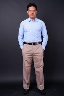 Studio shot van volwassen knappe indiase zakenman tegen zwarte achtergrond
