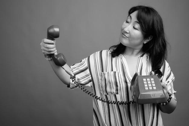 Studio shot van volwassen mooie japanse vrouw tegen grijs in zwart en wit