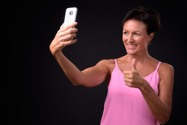 Studio shot van volwassen mooie scandinavische vrouw met kort haar tegen zwarte achtergrond