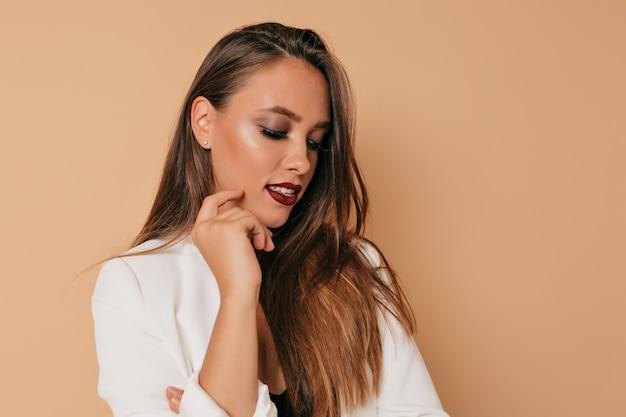 Studio shot van vrij europese vrouw met lichte make-up naar beneden te kijken met een glimlach op de achtergrond