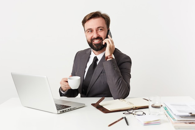 Studio shot van vrij positieve bebaarde brunette man met kort kapsel zittend aan de werktafel met kopje koffie, bellen met zijn smartphone en opzij kijken met een brede glimlach