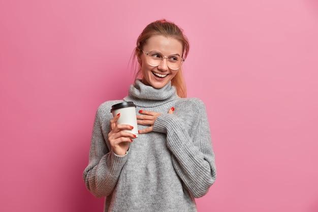 Studio shot van vrolijk europees meisje giechelt positief hand op de borst en houdt afhaalkoffie