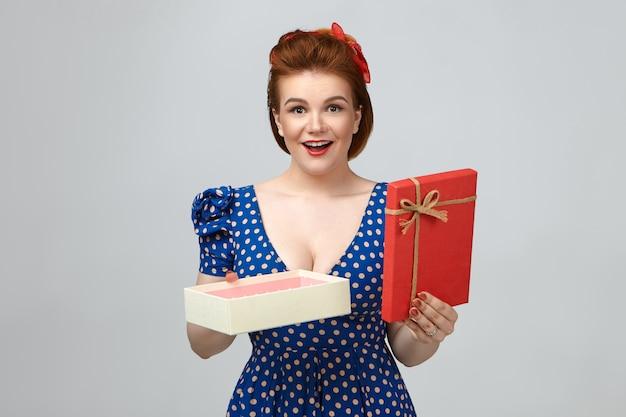 Studio shot van vrolijk feestvarken dragen retro kapsel en blauwe gestippelde jurk mond openen van verbazing, blij en opgewonden voelen, open doos vol chocoladesuikergoed op valentijnsdag houden