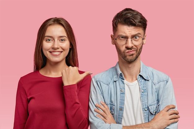 Studio shot van vrolijke brunette lachende vrouw wijst met duim naar haar ontevreden man die de handen gekruist houdt