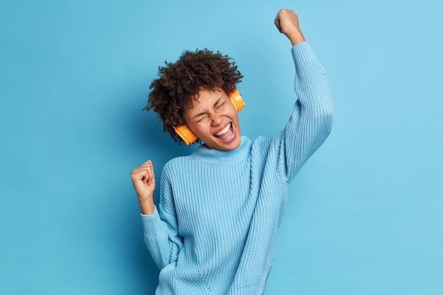 Studio shot van vrolijke donkerhuidige vrouw heft armen op en gebalde vuisten viert iets met triomf, luistert favoriete muziek via koptelefoon voelt als winnaar