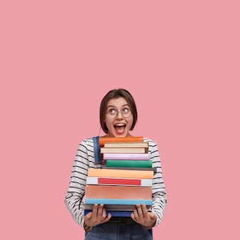 Studio shot van vrolijke europese vrouw draagt een ronde bril, heeft veel boeken