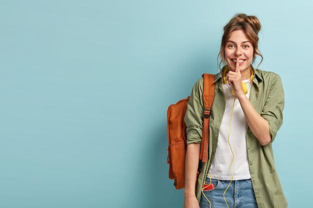 Studio shot van vrolijke europese vrouw maakt stilte gebaar