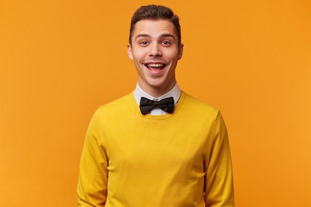 Studio shot van vrolijke gezellige jonge aantrekkelijke man, netjes gekleed in een gele trui met vlinderdas