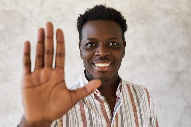 Studio shot van vrolijke jonge afrikaanse man breed glimlachend op camera, stopbord maken. knappe zwarte man in gestreept overhemd zegt hallo, groet vriend, met een blije blik