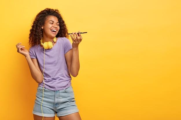 Studio shot van vrolijke jonge vrouw met afro kapsel poseren tegen de gele muur
