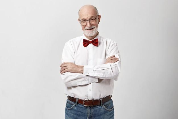 Studio shot van vrolijke knappe grootvader met baard en kale hoofd glimlachen