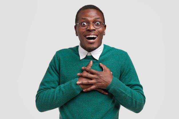 Studio shot van vrolijke man kijkt met verbazing en geluk, houdt de handen op de borst, gekleed in groene trui