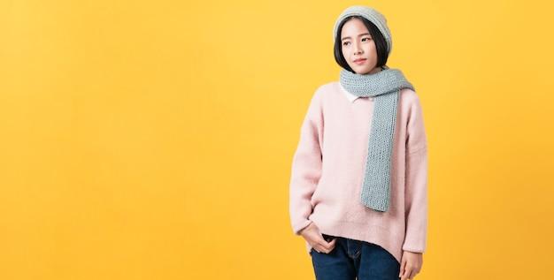 Studio shot van vrolijke mooie aziatische vrouw in lichte kleur t-shirt en staan op oranje muur.