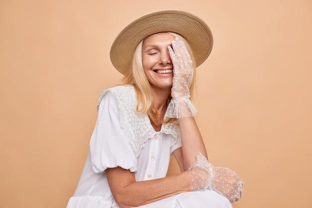 Studio shot van vrolijke zorgeloze blonde vrouw maakt gezicht palm lacht vrolijk om goede grap draagt hoed modieuze witte jurk en kanten handschoenen zit tegen beige muur