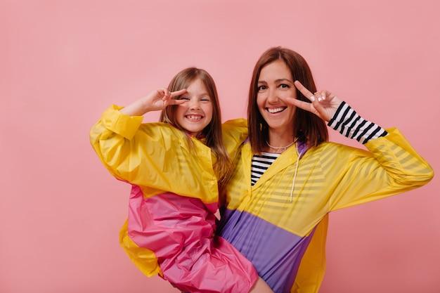 Studio shot van vrouw met charmant meisje dragen regenjassen vrede tekenen over geïsoleerde roze achtergrond