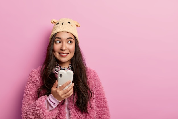 Studio shot van vrouwelijke blogger creëert eigen webblog, houdt moderne mobiele telefoons, gebruikt technologie, kijkt positief opzij, leest tekstbericht