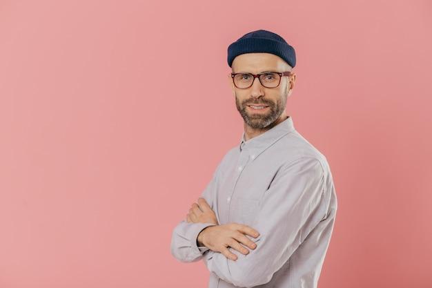 Studio shot van zelfverzekerde bebaarde man met blauwe ogen, draagt stijlvolle hoed en wit shirt, houdt armen over elkaar