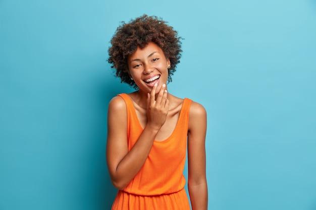 Studio shot van zorgeloze, vrolijke afro-amerikaanse vrouw kijkt vrolijk naar de camera
