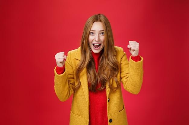 Studio shto van vrolijk opgewonden, goed uitziend gembermeisje in gele jas die gebalde vuisten opheft in vreugde en geluk, triomfantelijk ja zeggend van succes en triomf, overwinning op rode muur vierend.