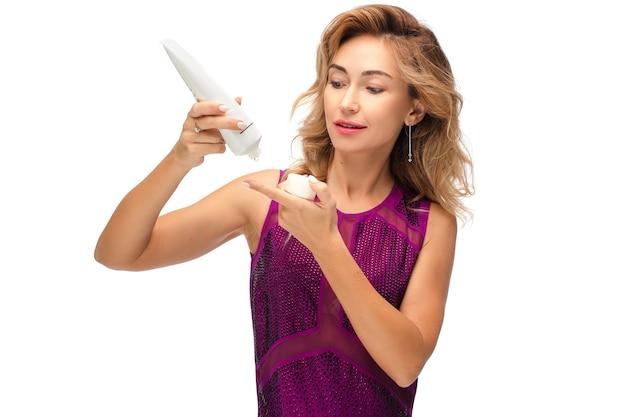 Studio stock foto van een prachtige jonge volwassen vrouw van in de dertig die opheffende crème uit de fles op haar vinger laat vallen. nieuw anti-verouderingsproduct testen. schoonheid en huidverzorging concept. isoleer op wit.