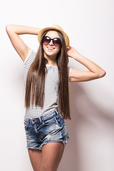 Studio weergave van vrolijke vrouw met brede glimlach, draagt trendy zonnebril, strooien hoed, zomerjurk, geïsoleerd over witte muur