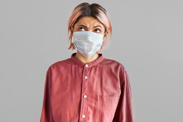 Studiobeeld van doordachte jonge europese vrouw met peinzende gezichtsuitdrukking die gezichtsmasker draagt dat is ontworpen om mensen te beschermen tegen het inademen van bacteriën of virussen in de lucht. coronavirus pandemie concept