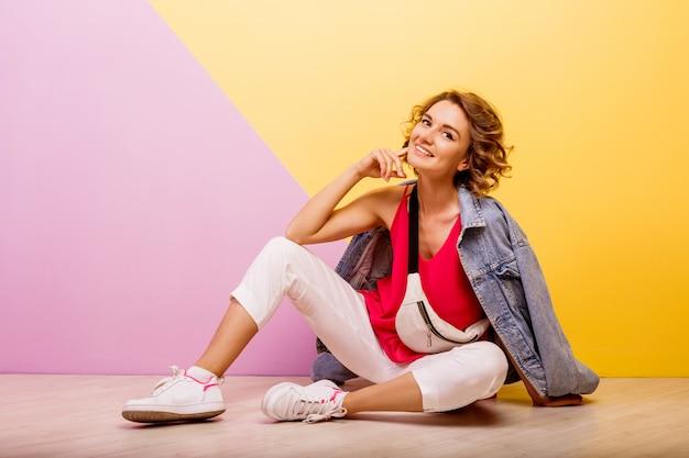 Studiobeeld van glimlachende donkerbruine mooie vrouw die modieuze sportieve uitrusting en jeansjasjezitting op de vloer dragen.