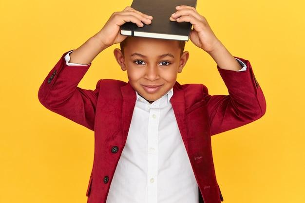 Studiobeeld van vrolijke stijlvolle donkere scholier met plezier, zwarte notitieboekje op het hoofd houden, camera kijken met een blije glimlach.