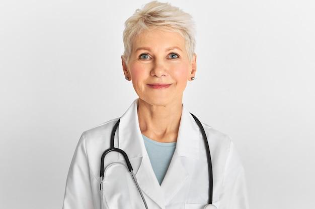Studiobeeld van zelfverzekerde aantrekkelijke vrouwelijke arts van middelbare leeftijd met kort geverfd kapsel poseren geïsoleerd met witte jas en stethoscoop.