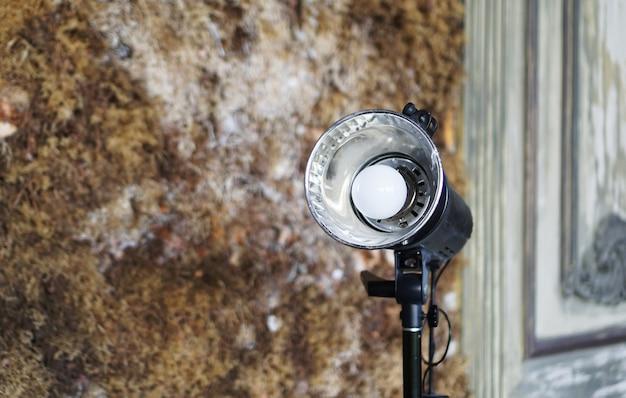Studioflitser tegen de achtergrond van een oude muur met mos