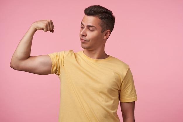 Studiofoto van de jonge knappe bruinharige man die trots naar zijn hand kijkt terwijl hij zijn sterke biceps demonstreert, staande over de roze achtergrond in vrijetijdskleding