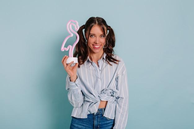 Studiofoto van een geïnspireerde dame die met een glimlach poseert en roze flamingo boven blauwe muur houdt. indoor portret van ontspannen jong meisje