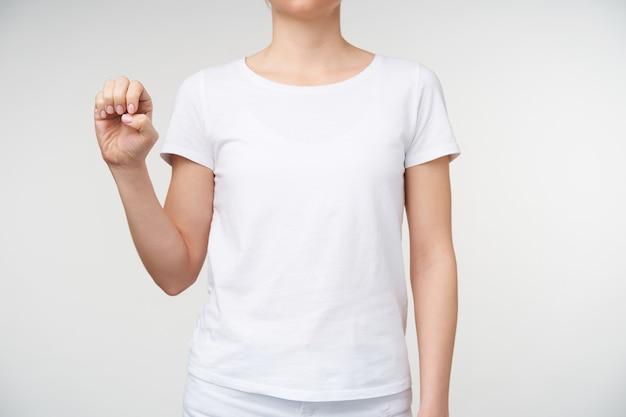 Studiofoto van een jonge blanke vrouw die doof alfabet leert en letter e vormt met opgeheven hand terwijl ze op een witte achtergrond in vrijetijdskleding staat