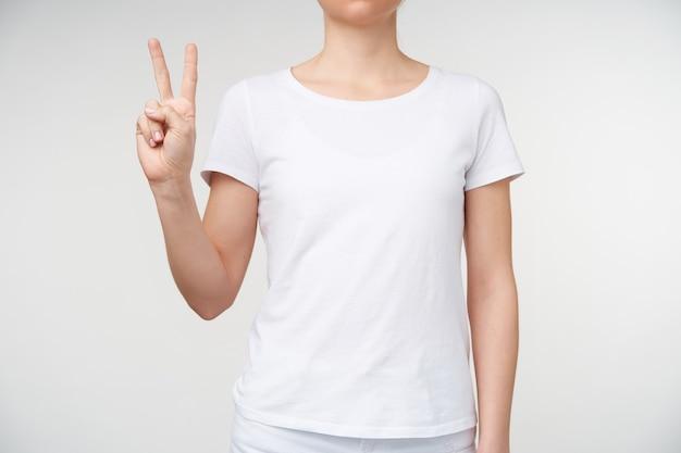 Studiofoto van een jonge dame die twee vingers toont terwijl ze vredesgebaar vormt, gebarentaal gebruikt om letter v aan te duiden, staande op een witte achtergrond