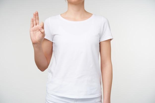 Studiofoto van een jonge dame gekleed in vrijetijdskleding die de hand omhoog houdt terwijl ze de letter f met doof alfabet laat zien, staande tegen een witte achtergrond
